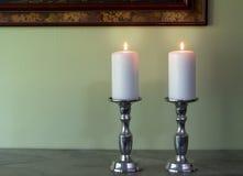 Due hanno acceso le candele bianche in canelabra contro le sedere verdi di struttura della parete Immagine Stock Libera da Diritti