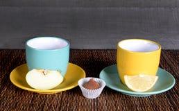 Due hanno colorato le tazze e le tazze su un fondo di legno con i frutti Fotografie Stock