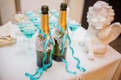 Due hanno decorato le bottiglie che stanno sulla tavola di nozze immagini stock