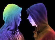 Due hanno disturbato gli adolescenti con la maglia con cappuccio nera che sta davanti ad a vicenda nel profilo isolati su fondo n immagine stock libera da diritti