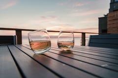 Due hanno inclinato i vetri della chiavetta di whiskey sulla tavola della piattaforma Fotografie Stock