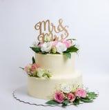 Due hanno messo a strati la torta di formaggio crema di nozze con le rose e l'eustoma Fotografia Stock Libera da Diritti