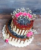Due hanno messo a strati la torta nunziale con i mirtilli, ribes del gocciolamento di colore Fotografia Stock