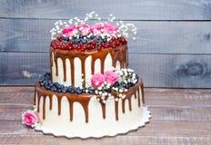 Due hanno messo a strati la torta nunziale con i mirtilli, ribes del gocciolamento di colore Immagine Stock