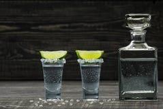 Due hanno sparato della tequila d'argento fredda un fondo di legno nero Immagine Stock Libera da Diritti