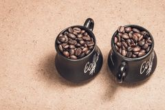 Due hanno tonificato le tazze con i chicchi di caffè su legno Fotografia Stock