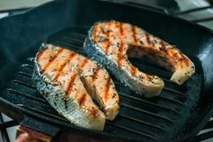 Due due hanno tostato le bistecche di color salmone con le spezie e le erbe su una griglia p fotografia stock libera da diritti