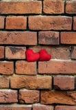 Due hanno tricottato il cuore rosso su una parete strutturata vecchia di sbriciolatura del mattone rosso Immagini Stock