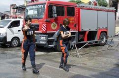Due hanno uniformato i combattenti di fuoco di signora che camminano in camion dei vigili del fuoco parcheggiato fotografia stock libera da diritti
