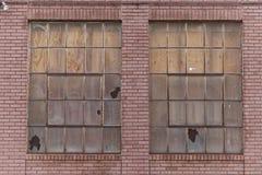 Due imbarcati e finestre rotte sul muro di mattoni rosso invecchiato immagine stock libera da diritti