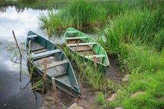 Due imbarcazioni a remi sulla riva fangosa del lago Fotografie Stock Libere da Diritti