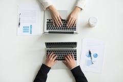 Due impiegati di concetto che scrivono sui computer portatili, vista alta vicina della cima Fotografia Stock
