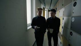 Due impiegati di concetto maschii che passano tramite il corridoio con gli armadi stock footage