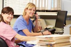 Due infermieri che lavorano alla stazione degli infermieri Fotografie Stock Libere da Diritti