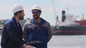 Due ingegneri con il computer portatile comunicano nel porto del carico di trasporto video d archivio