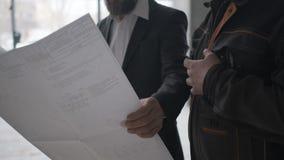 Due ingegneri si incontrano a costruzione e consultano il progetto di costruzione Due assistenti tecnici Fine in su video d archivio