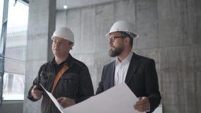 Due ingegneri si incontrano a costruzione e consultano il progetto di costruzione Due assistenti tecnici stock footage