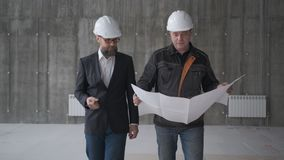 Due ingegneri si incontrano a costruzione e consultano il progetto di costruzione Due assistenti tecnici archivi video
