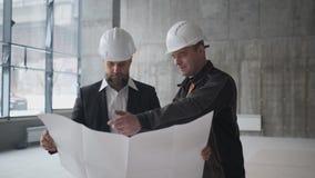 Due ingegneri si incontrano a costruzione e consultano il progetto di costruzione Due assistenti tecnici video d archivio