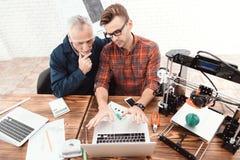 Due ingegneri sono impegnati nella progettazione dei modelli per una stampante 3d Lavorano ai loro computer portatili nell'aborto Immagini Stock
