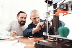 Due ingegneri stampano i dettagli sulla stampante 3d Un uomo degli anziani controlla il processo Fotografia Stock Libera da Diritti