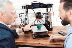 Due ingegneri stanno stampando un modello della mela su una stampante 3d Esaminano il risultato del lavoro della stampante 3d Fotografia Stock Libera da Diritti