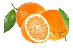 Due interi ed a metà arancio con la foglia isolata su bianco Fotografia Stock Libera da Diritti