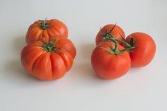 Due interi pomodori della bistecca parallelamente con tre interi pomodori della capriata Immagini Stock