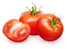 Due interi pomodori rossi freschi con le foglie verdi e mezzi Fotografie Stock Libere da Diritti