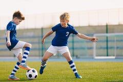 Due Junior Soccer Players Training con pallone da calcio sul passo dell'erba dello stadio immagine stock
