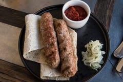 Due kebab di lula sul pane della pita con le cipolle e la salsa al pomodoro rossa immagini stock libere da diritti
