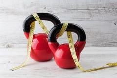 Due kettlebells rossi con nastro adesivo di misurazione Fotografia Stock