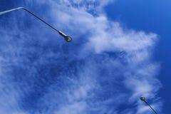 Due lampade dell'iluminazione pubblica con i precedenti del cielo blu e della nuvola fotografia stock libera da diritti