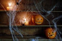 Due lanterne di Jack o hanno scolpito dalle arance sullo scaffale Fotografia Stock