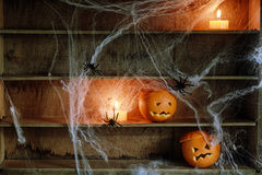 Due lanterne di Jack o hanno scolpito dalle arance sullo scaffale Fotografie Stock