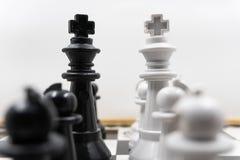 Due lati dei pezzi degli scacchi con re neri e re bianchi ed i loro pegni che si affrontano C'? un fondo bianco per fotografia stock