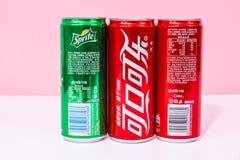 Due latte di Coca-Cola e di uno possono Sprite scritta in cinese immagini stock
