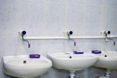 Due lavandini bianchi e sapone liquido nella toilette pubblica immagini stock
