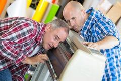 Due lavoratori allegri positivi che lavorano alla macchina Fotografia Stock