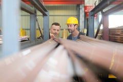 Due lavoratori che cercano i profili specifici del PVC nel magazzino della fabbrica Immagini Stock