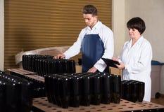 Due lavoratori che controllano numero delle bottiglie di vino al vino spumante Immagine Stock Libera da Diritti