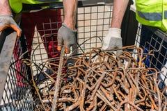 Due lavoratori che controllano un mucchio delle barre d'acciaio arrugginite Fotografia Stock