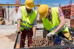 Due lavoratori che controllano un mucchio delle barre d'acciaio arrugginite durante il lavoro sulla t Fotografie Stock Libere da Diritti