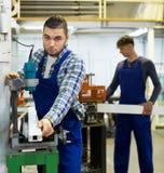Due lavoratori che lavorano ad una macchina Immagine Stock