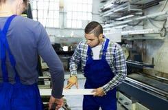 Due lavoratori che lavorano ad una macchina Immagini Stock