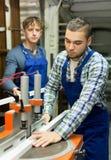 Due lavoratori che lavorano ad una macchina Immagini Stock Libere da Diritti