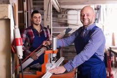 Due lavoratori che lavorano alla macchina Immagine Stock