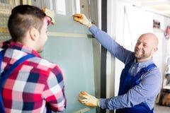 Due lavoratori che lavorano con il vetro immagine stock