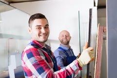 Due lavoratori che lavorano con il vetro fotografie stock