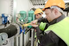Due lavoratori che riparano i tubi Immagini Stock